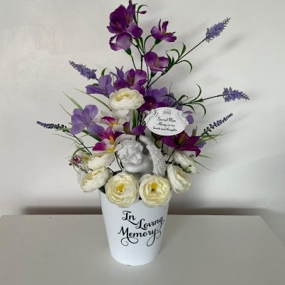 Hand made grave flowers arrangement in white roses with purple additions.